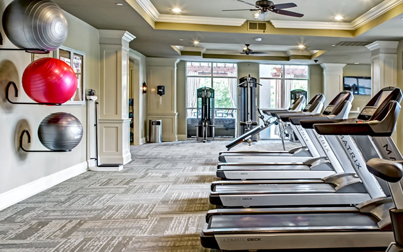 spacious fitness center with ceiling fans and recessed lighting